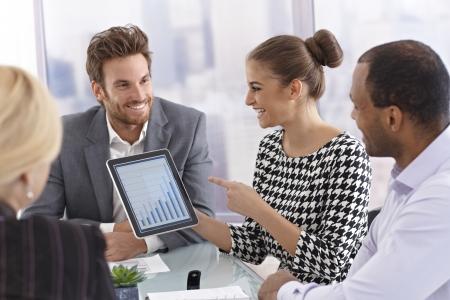 sala de reuniões: Empresária jovem e atraente usando tablet para apresentar diagrama de negócios em uma reunião.