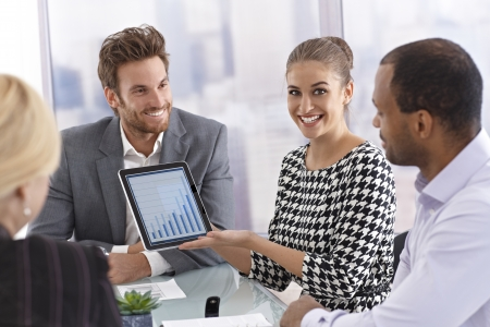 explaining: Beautiful young businesswoman using tablet computer at a business meeting, smiling happy. Stock Photo