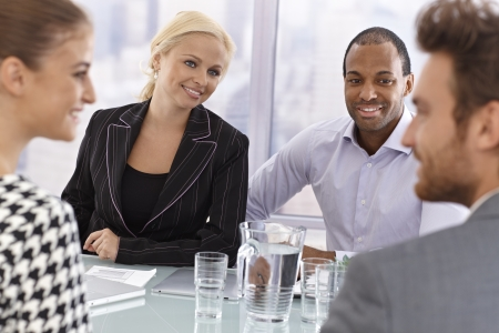 businessmeeting: Young partners having businessmeeting, smiling happy. Stock Photo