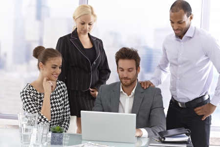 Young businesspeople in meetingroom, looking at laptop computer. Stock Photo - 17133929