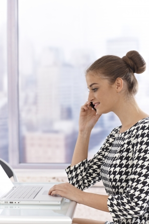 Side view of attractive young businesswoman sitting at table, using laptop computer, talking on mobile phone. Stock Photo - 17134033