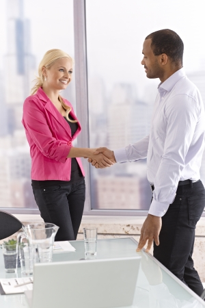 view of an elegant office: Young female and male business partners shaking hands, smiling.