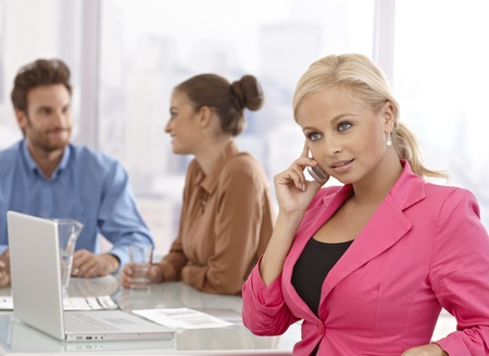 businessmeeting: Young businesswoman talking on mobilephone at businessmeeting.
