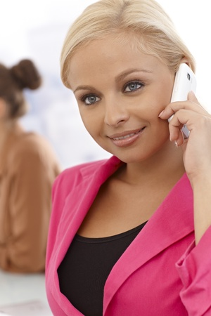 Closeup portrait of attractive young businesswoman talking on cellphone, smiling. photo