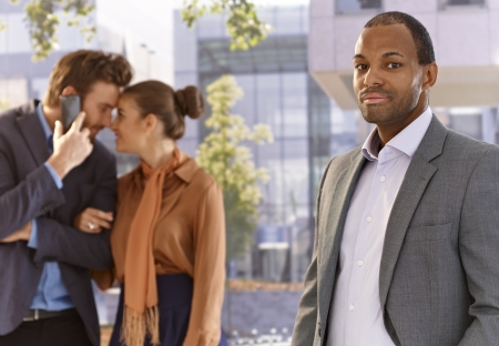 Portrait of serious afro businessman front of skyscrapers, young couple at background. Stock Photo - 17133959