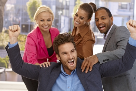 Handsome businessman celebrating success with young colleagues. Stock Photo - 17133930