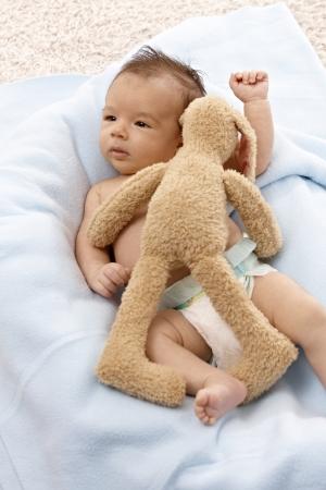 Beautiful newborn baby lying naked with plush bunny. Stock Photo - 17159644