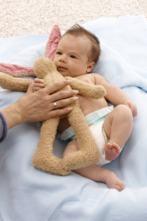 Lovely infant laying naked with plush bunny. Stock Photo - 17159650