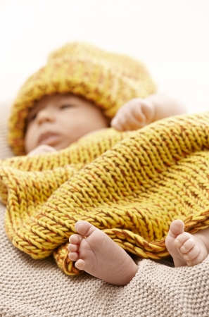 Newborn baby in knitwear. Focus on barefoot. photo