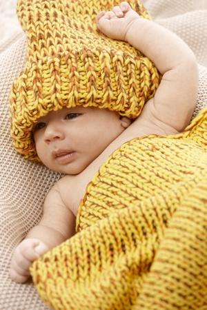 tejidos de punto: Precioso beb� reci�n nacido en prendas de punto amarillo.