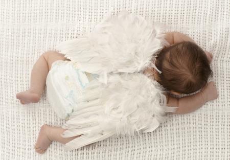 baby angel: Bambino piccolo sdraiato sul fronte, vestita di bianco di piume ali d'angelo. Archivio Fotografico