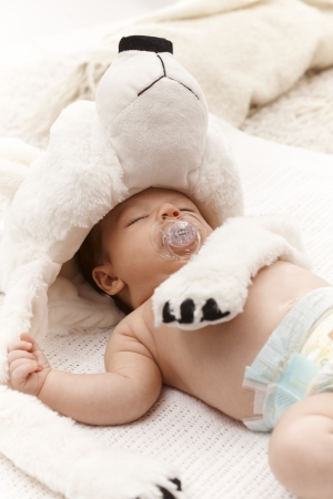 Adorable sleeping infant with dummy and big bear hat. Stock Photo - 17159688