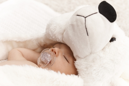 Closeup photo of beautiful baby with dummy and big bear hat. Stock Photo - 17159677