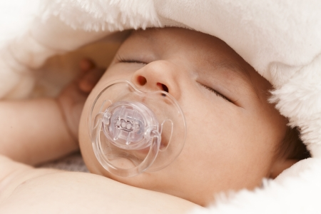 Closeup photo of adorable newborn baby sleeping with dummy. Stock Photo - 17159643