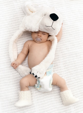Lovely newborn baby sleeping with dummy, wearing big bear hat and knitted boots. Stock Photo - 17159648