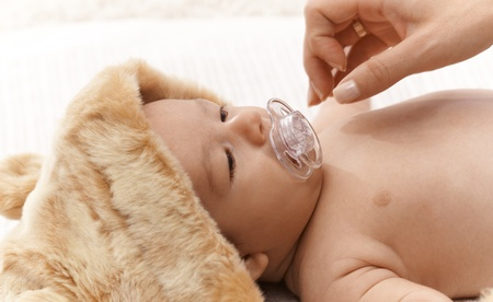 Lovely newborn baby in fur cap with dummy. Stock Photo - 17159672