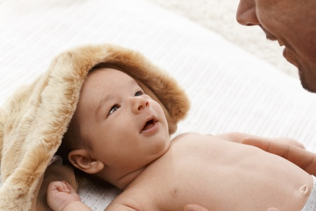 Smiling newborn baby lying naked, looking at father. Stock Photo - 17159642