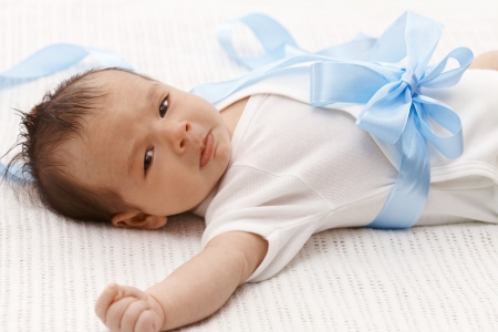 Lovely baby boy in white bodysuit and big blue bow starting to cry. photo
