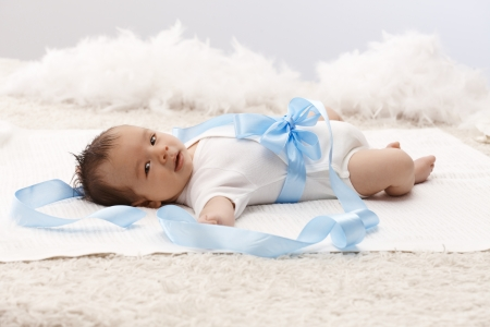 Beautiful baby lying on back in white bodysuit and blue ribbon around waist. photo