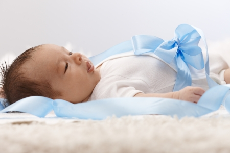 Side view of lovely newborn baby with big bow on belly in white and light blue. photo