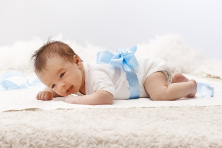 Newborn baby lying on front in white bodysuit and blue ribbon around waist, lifting head. Stock Photo - 17159680