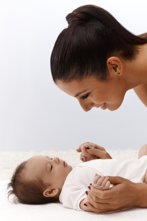 Infant lying on back, mother smiling happy leaning over baby, looking close. Stock Photo - 17159641