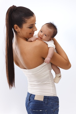 Pretty young mother holding newborn baby in arm, embracing, smiling happy. photo