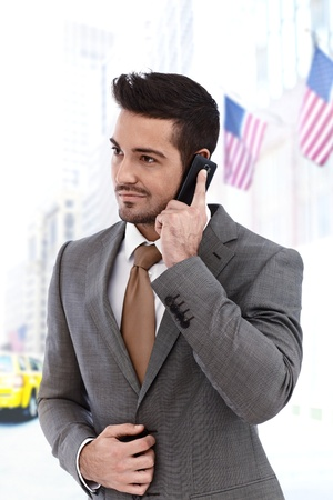 looking away: Young businessman on the phone walking outdoors, american flags in background Stock Photo