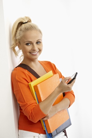 Young female student smiling happy, holding folders, using mobile. photo
