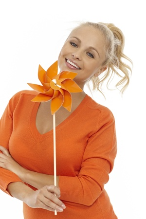 Happy blonde girl holding pinwheel, smiling. Stock Photo - 17193845