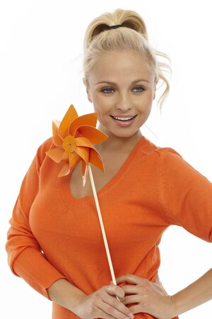 Pretty young blonde girl holding pinwheel, smiling. photo