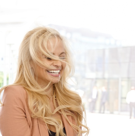 Blond woman laughing outdoors, wind blowing her hair. photo