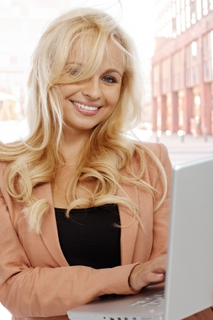 Young blond businesswoman using laptop on street, looking at camera smiling. photo