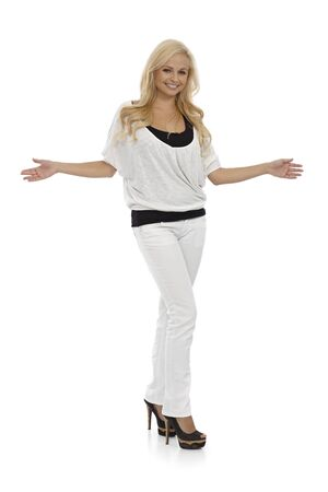 outspreading: Happy young blonde woman standing with arms wide open, full size.