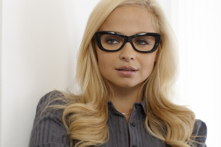 black hair blue eyes: Closeup portrait of attractive blonde woman with black framed glasses.
