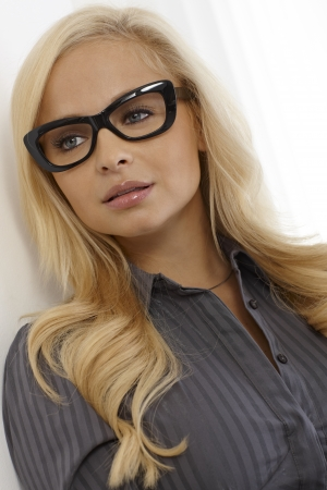 Beautiful blonde woman in black framed characterisctic glasses, looking away. photo
