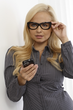 Pretty blonde woman in black framed glasses using mobile phone. photo