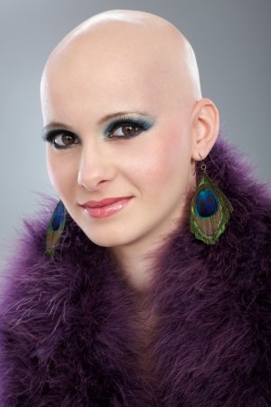Beauty portrait of hairless woman in purple boa, looking at camera, smiling. photo