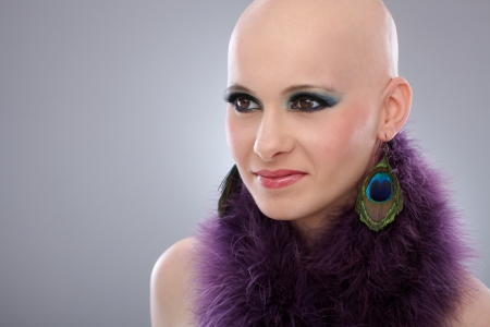 Beauty portrait of hairless woman in purple boa. photo