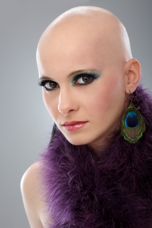 Beauty portrait of hairless woman in purple boa, looking at camera. photo