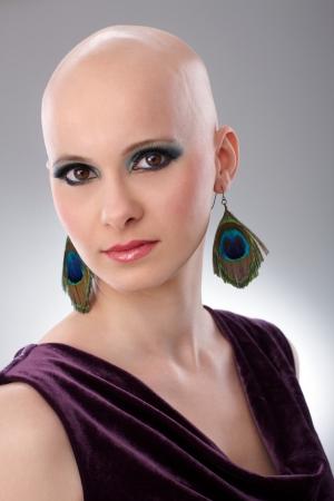 velvet dress: Studio portrait of hairless woman wearing elegant claret velvet dress.
