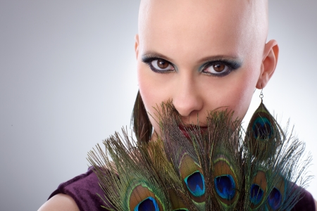 stockphoto: Portrait of beautiful hairless woman using peacock plumes as accessory.
