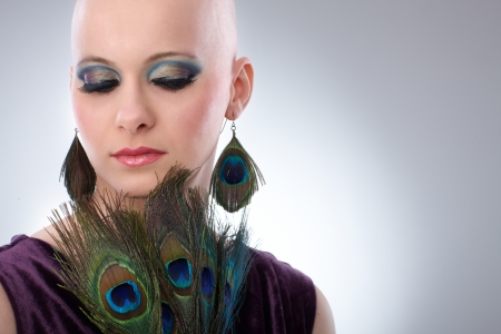 Portrait of beautiful hairless woman using peacock plumes as accessory   65533; photo