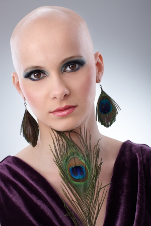 25 30 years women: Portrait of beautiful hairless woman using peacock plumes as accessory