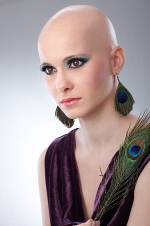 hairless: Portrait of beautiful hairless woman using peacock plumes as accessory   65533;
