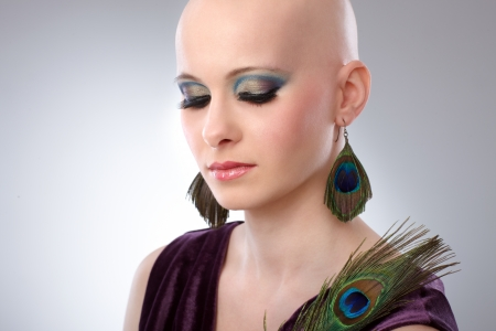 Portrait of beautiful hairless woman using peacock plumes as accessory    photo
