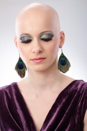 velvet dress: Studio portrait of hairless woman wearing elegant claret velvet dress