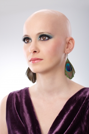 velvet dress: Studio portrait of bald woman wearing elegant claret velvet dress