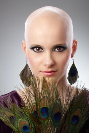 calvo: Retrato de la mujer hermosa sin pelo con plumas de pavo real como accesorio.