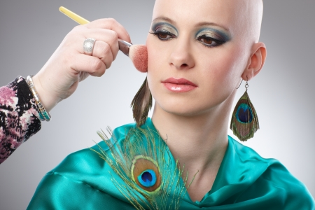 Hand working on makeup of hairless woman   65533; photo